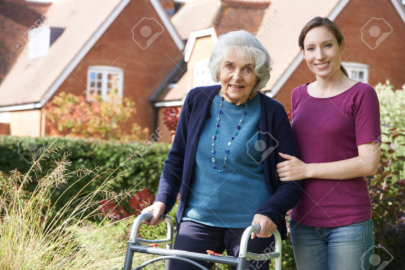 Daughter Helping Senior Mother To Use Walking Frame Banque d'images - 54532356