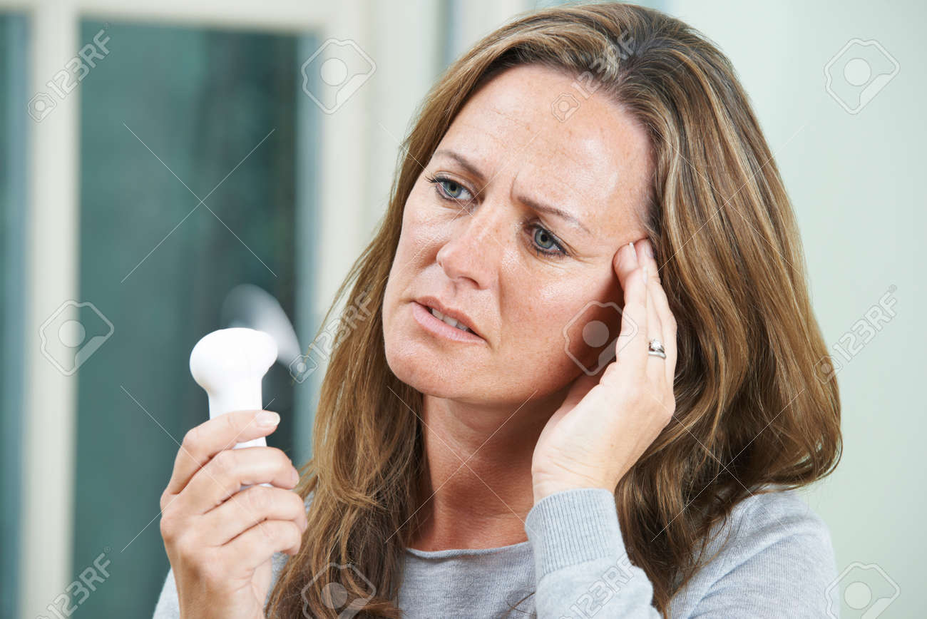 Mature Woman Experiencing Hot Flush From Menopause - 54861242
