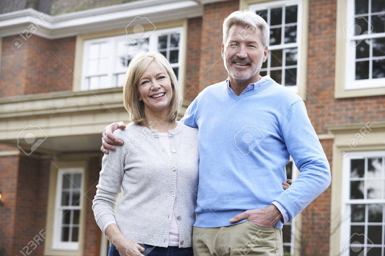 Portrait Of Mature Couple Standing Outside Home - 54904748