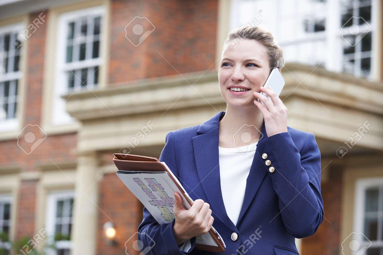 Female Realtor On Phone Outside Residential Property - 54904762