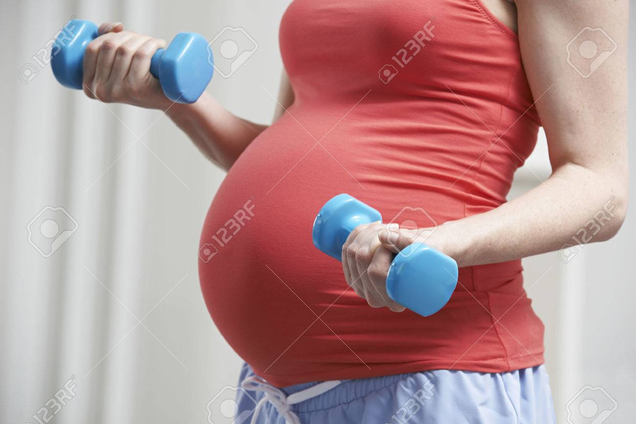 Close Up Of Pregnant Woman Exercising With Weights - 54905032