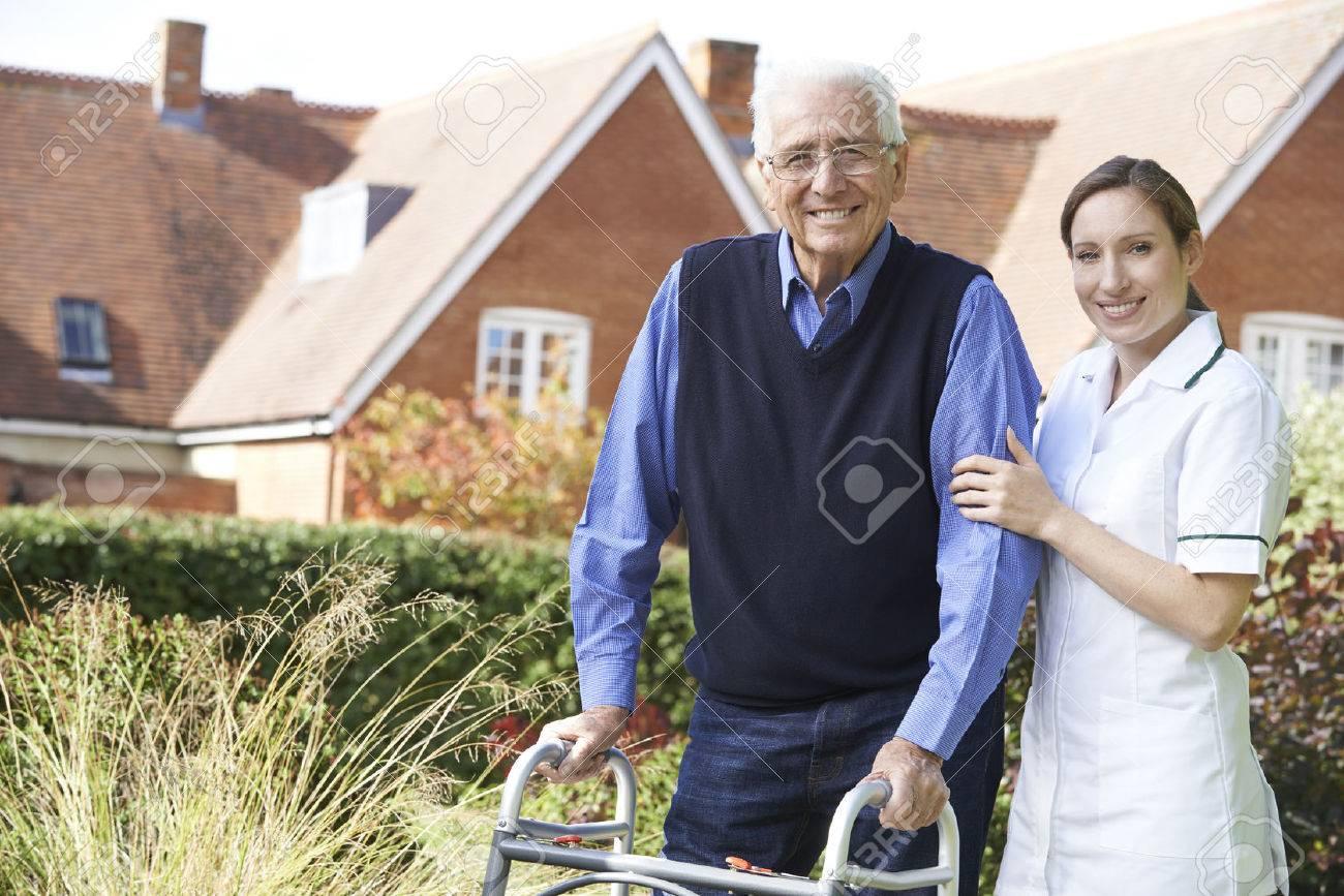 Carer Helping Senior Man To Walk In Garden Using Walking Frame Banque d'images - 54906616