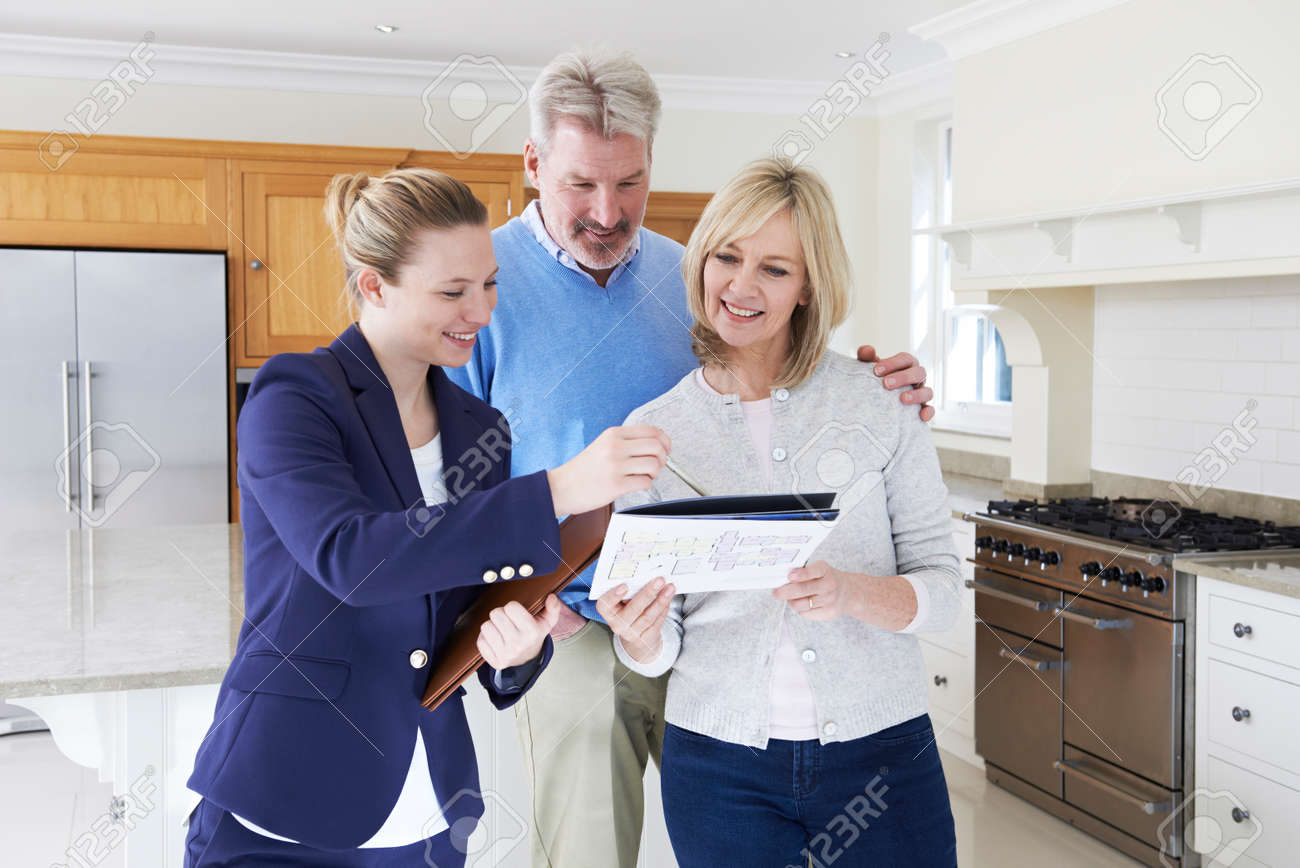 Female Realtor Showing Mature Couple Around New Home Banque d'images - 54906785