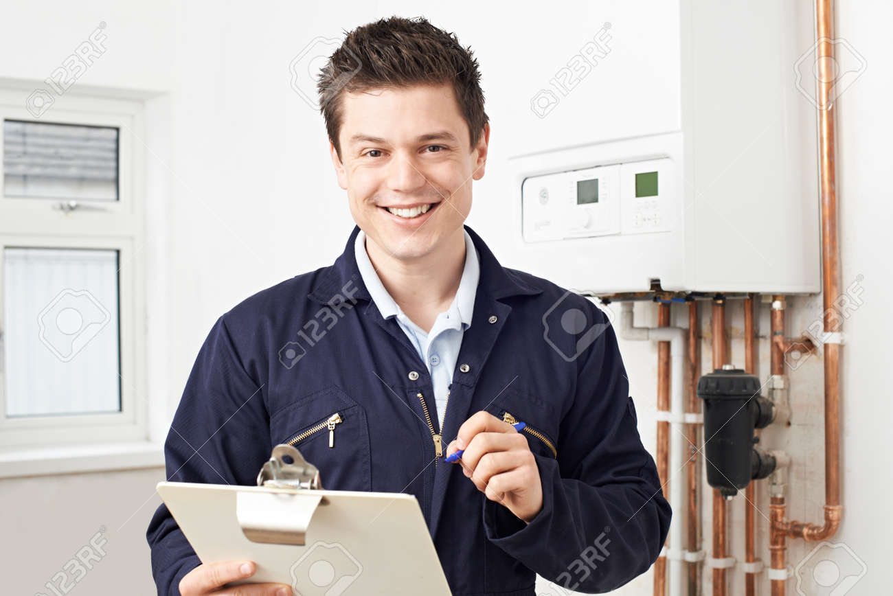 Male Plumber Working On Central Heating Boiler - 56216472