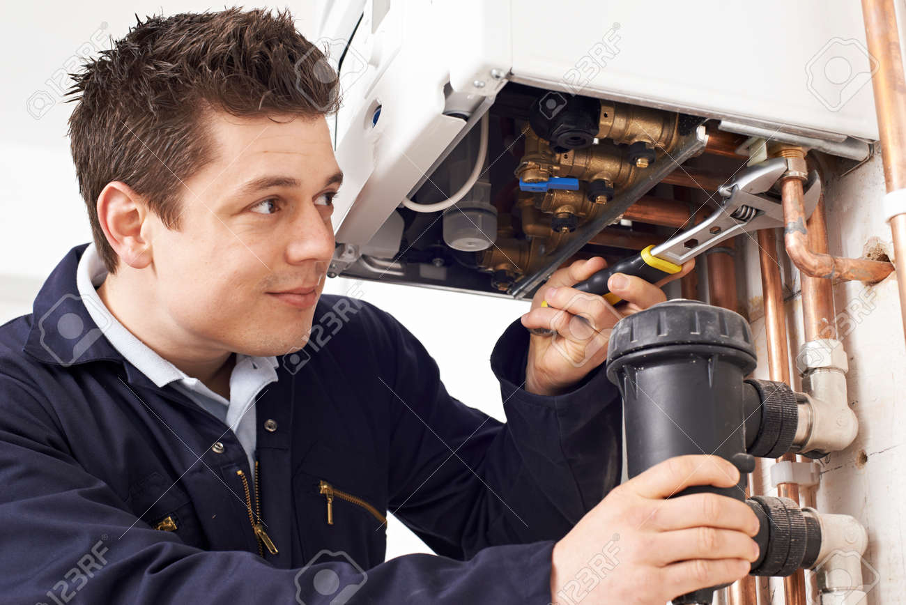 Male Plumber Working On Central Heating Boiler - 56216441