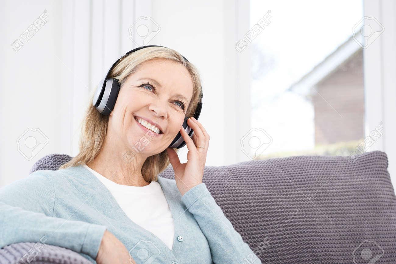 Femme Dâge Mûr écouter De La Musique Sur Un Casque Sans Fil Banque