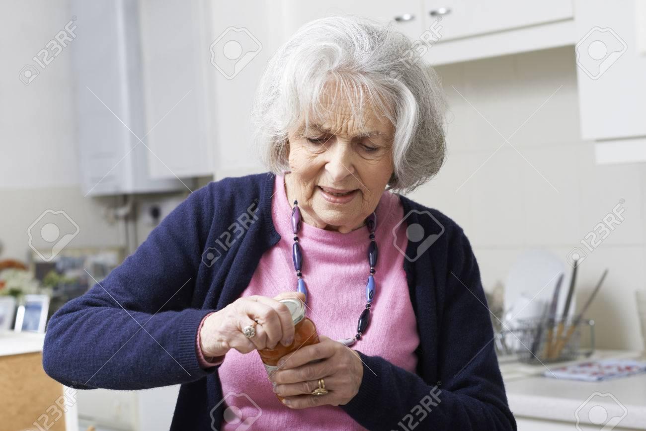 Senior Woman Struggling To Take Lid Off Jar - 57482778