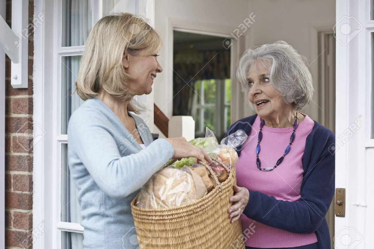 Female Neighbor Helping Senior Woman With Shopping - 57482854