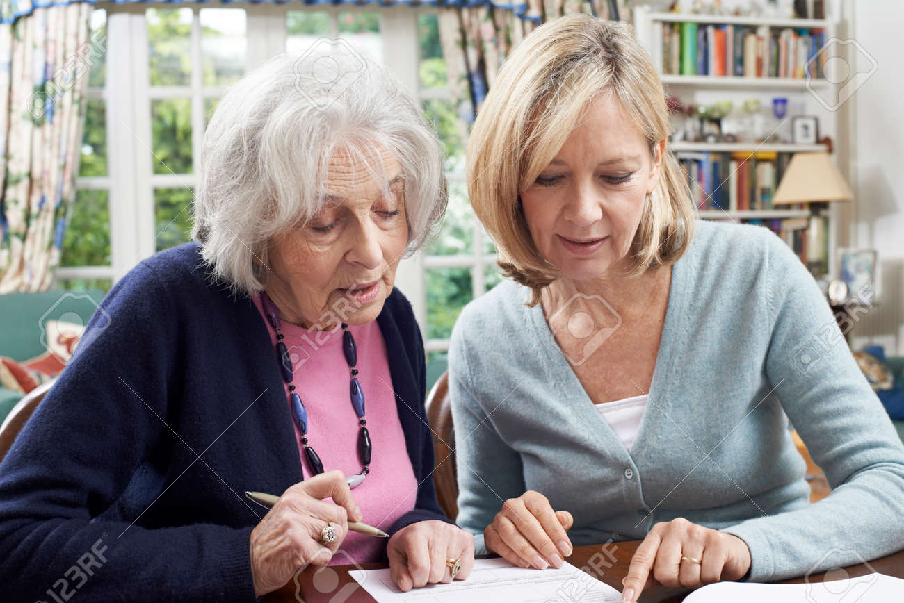 Female Neighbor Helping Senior Woman To Complete Form - 57482990
