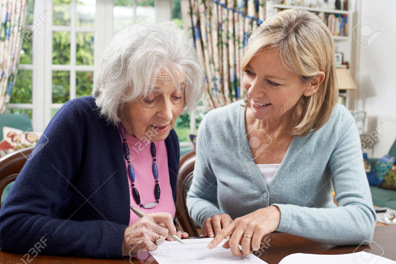 Female Neighbor Helping Senior Woman To Complete Form - 61674039