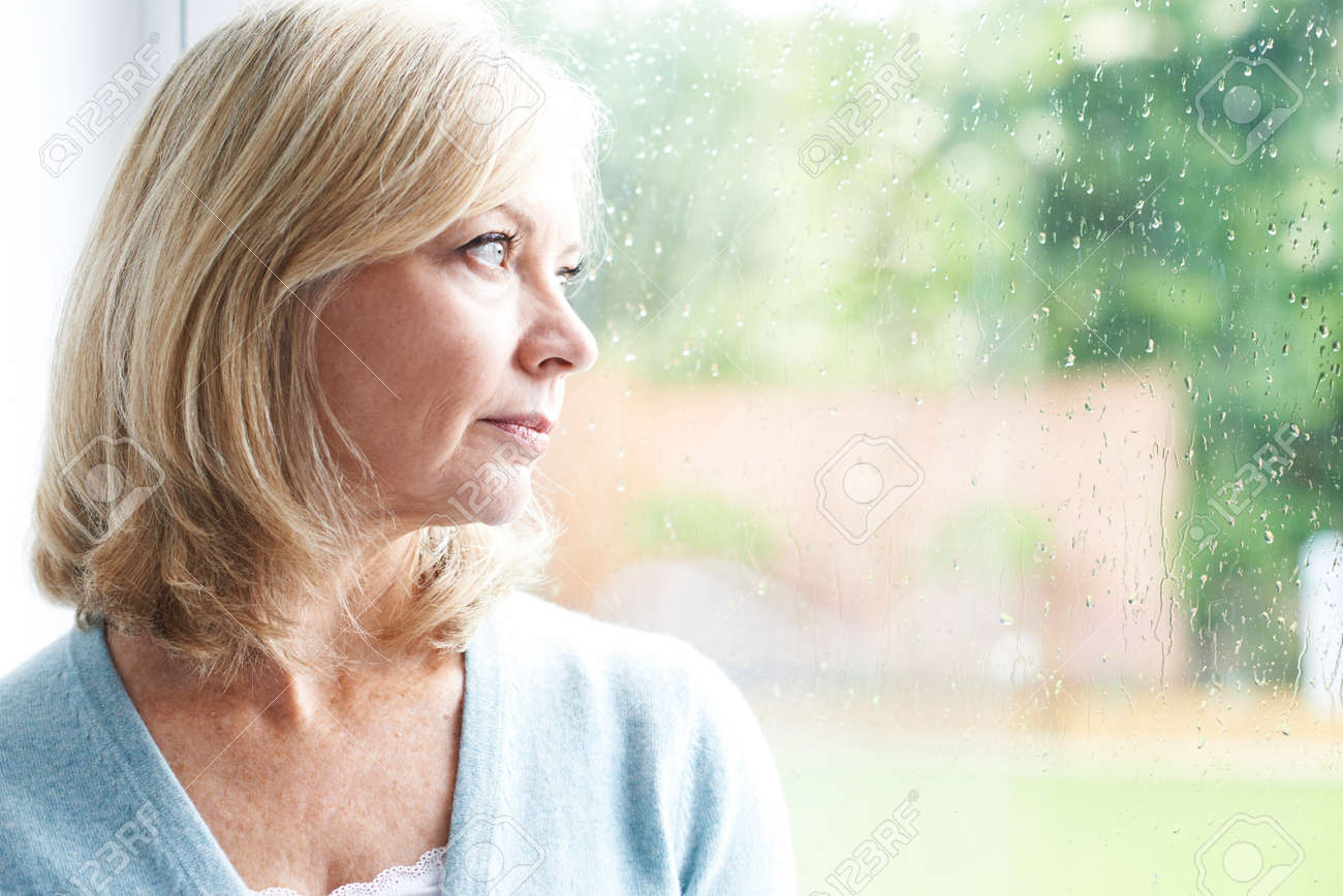 Sad Mature Woman Suffering From Agoraphobia Looking Out Of Window Banque d'images - 60774413