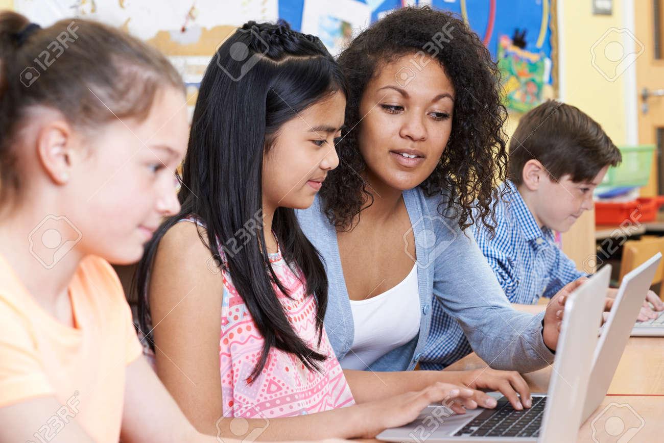 Enseignant Aider Groupe de l'école primaire des enfants en classe informatique Banque d'images - 60965001
