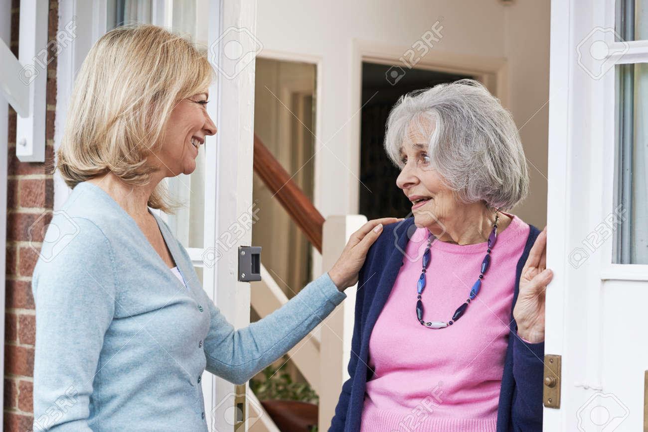 Woman Checking On Elderly Female Neighbor - 61702831