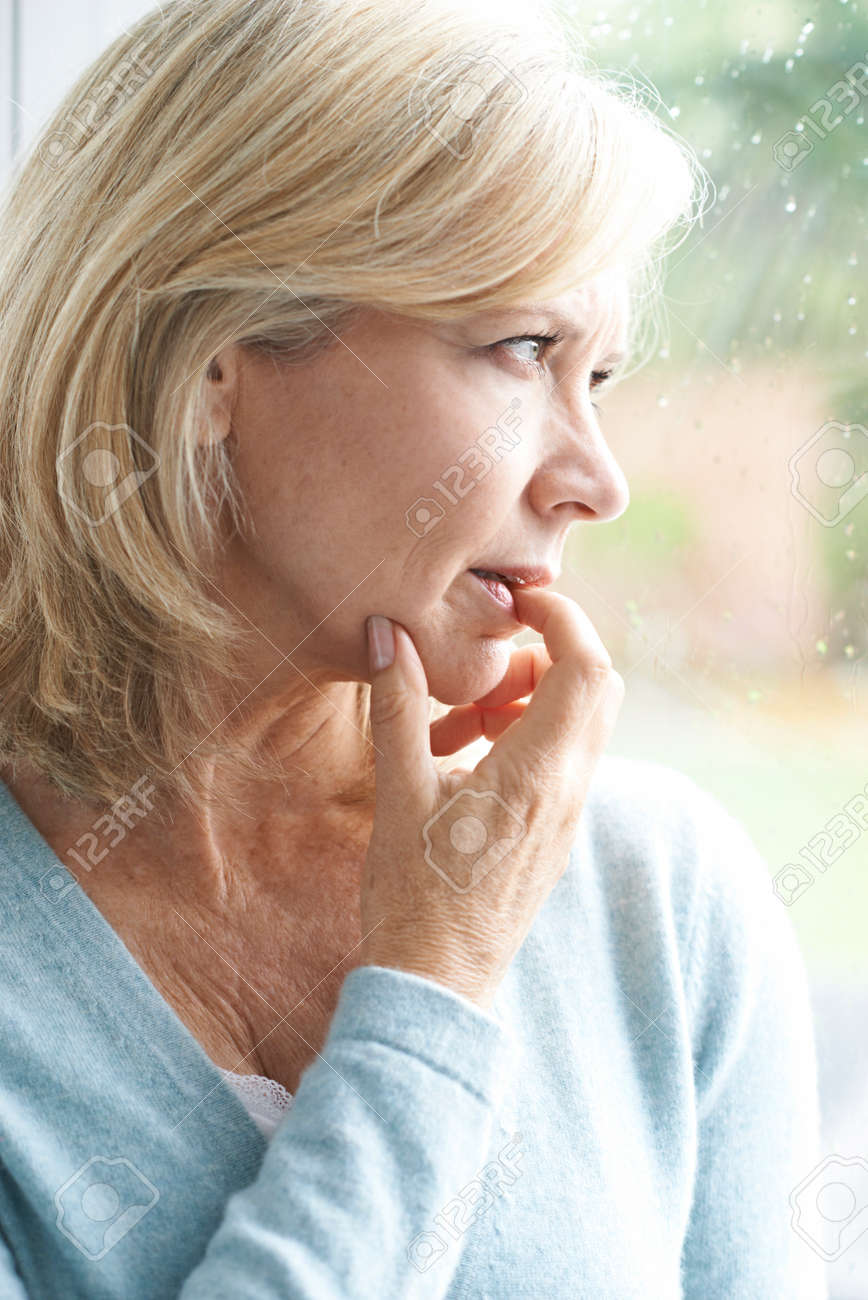 Sad Mature Woman Suffering From Agoraphobia Looking Out Of Window - 60965198
