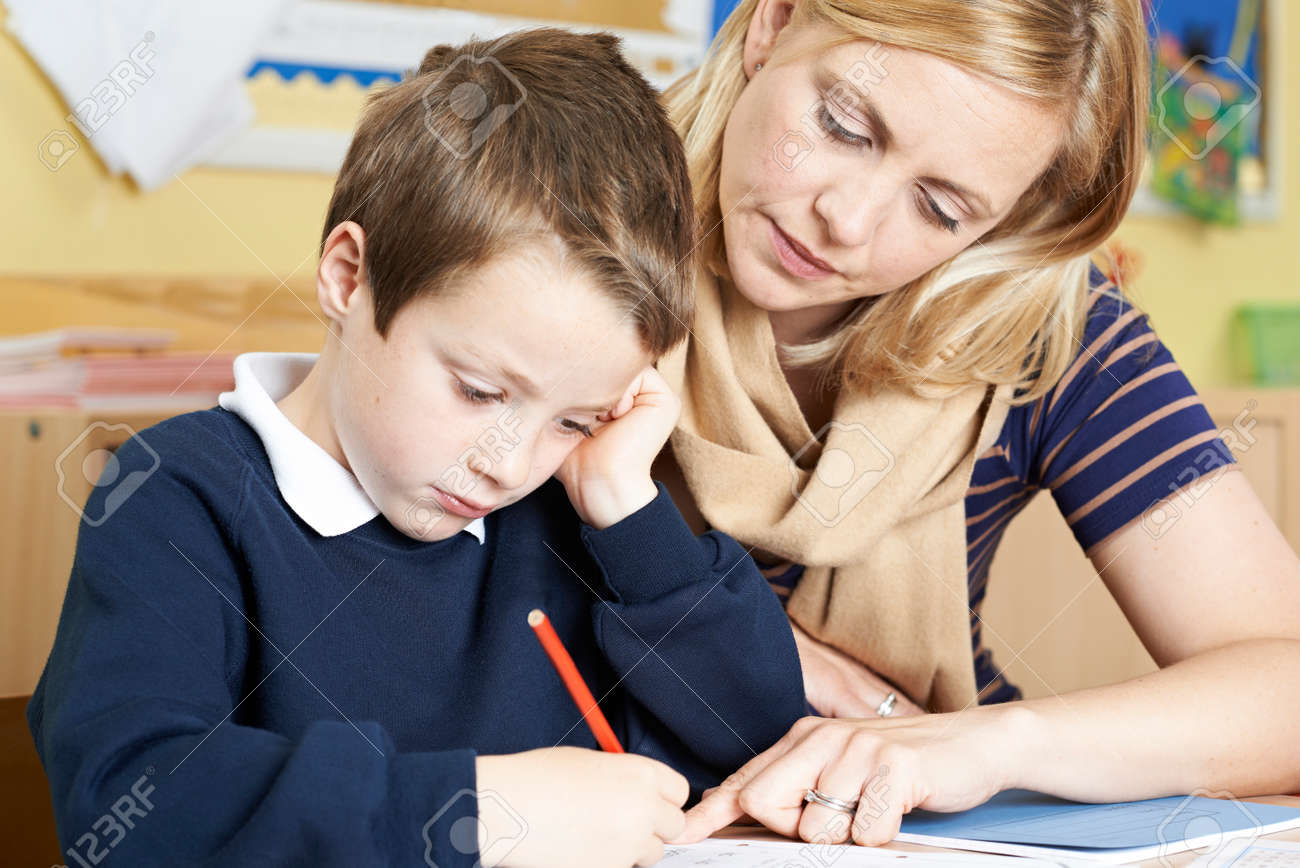 Teacher With Male Elementary School Pupil With Problem - 61521251
