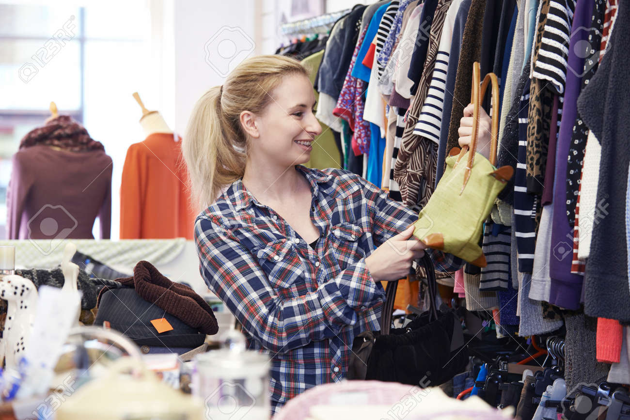 Female Shopper In Thrift Store Looking At Handbags - 62000350