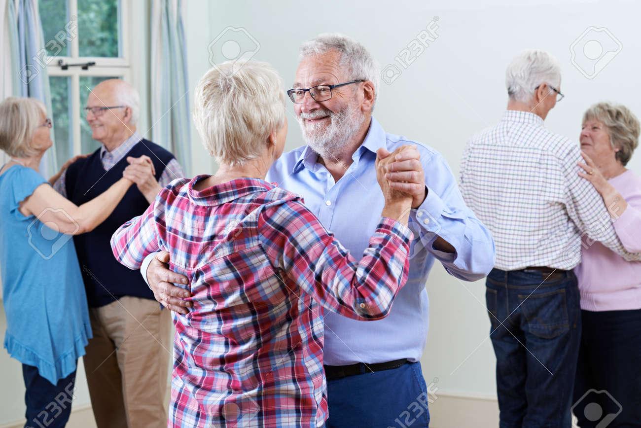 Group Of Seniors Enjoying Dancing Club Together - 64168234