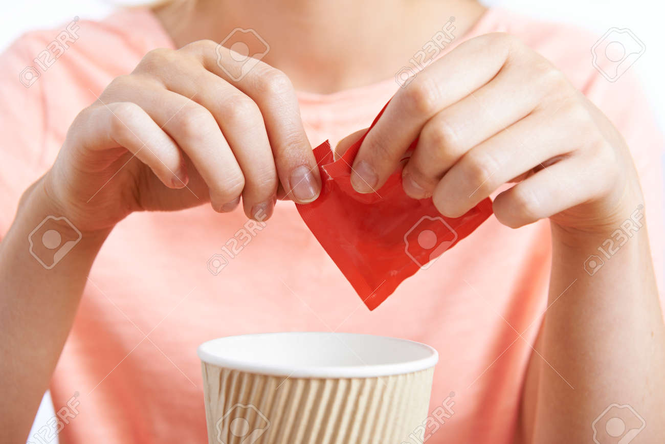Woman Adding Artificial Sweetener To Coffee Banque d'images - 64168161