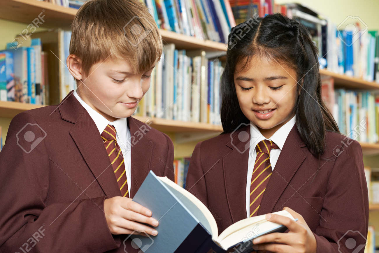 Pupils Wearing School Uniform Reading Book In Library - 63089861