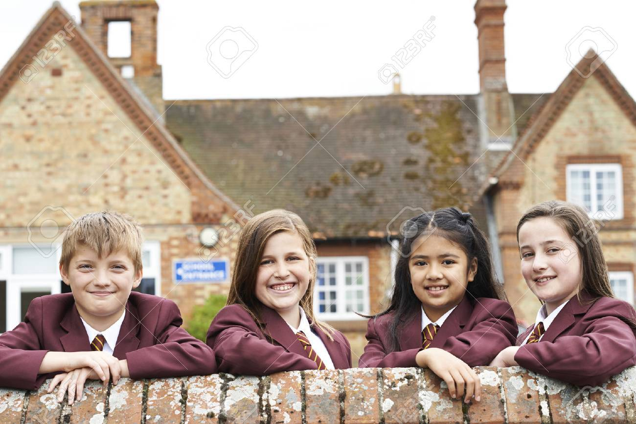 Portrait Of Pupils In Uniform Outside School Building - 63034793
