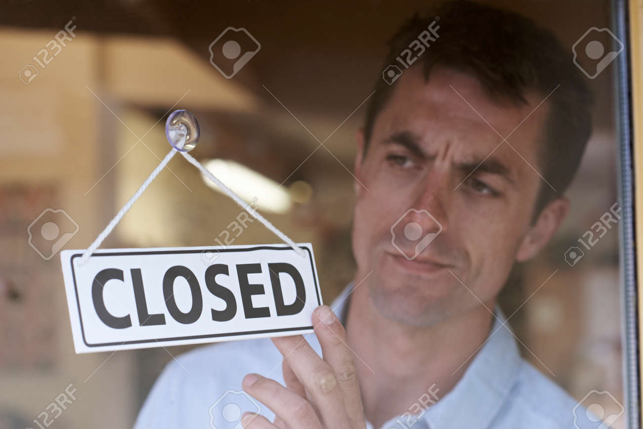 Store Owner Turning Closed Sign In Shop Doorway Banque d'images - 65620548