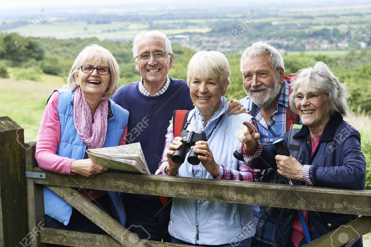 Group Of Senior Friends Hiking In Countryside Banque d'images - 65620549