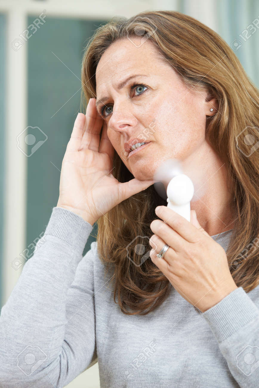 Mature Woman Experiencing Hot Flush From Menopause Stock Photo - 65624499
