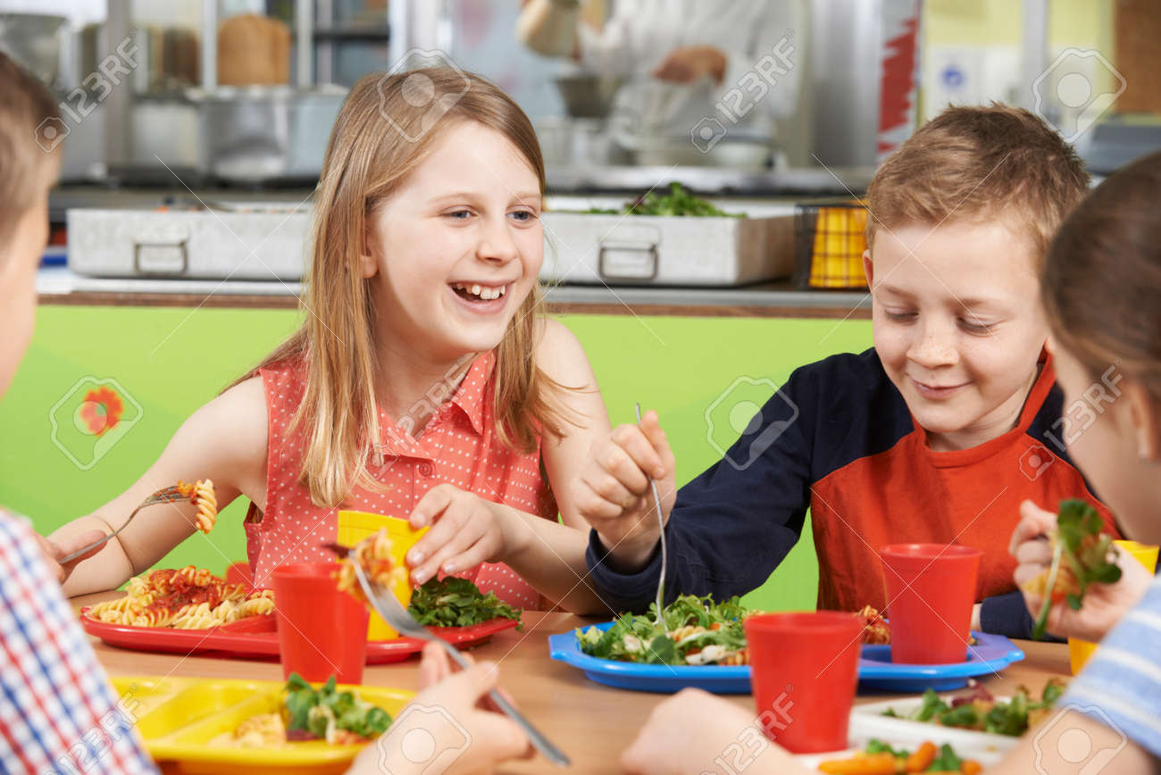 Group Of Pupils Sitting At Table In School Cafeteria Eating Lunch - 67037755