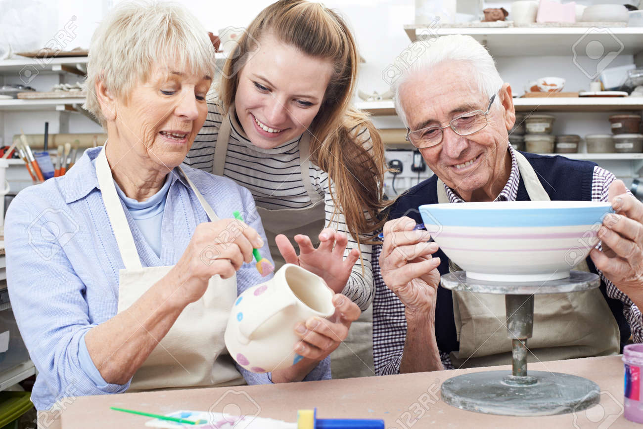 Senior Couple With Teacher In Pottery Class - 70616975