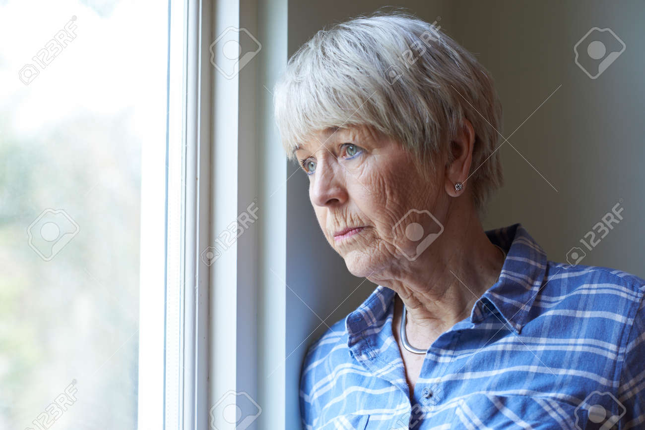 Senior Woman Suffering From Depression Looking Out Of Window - 71624625