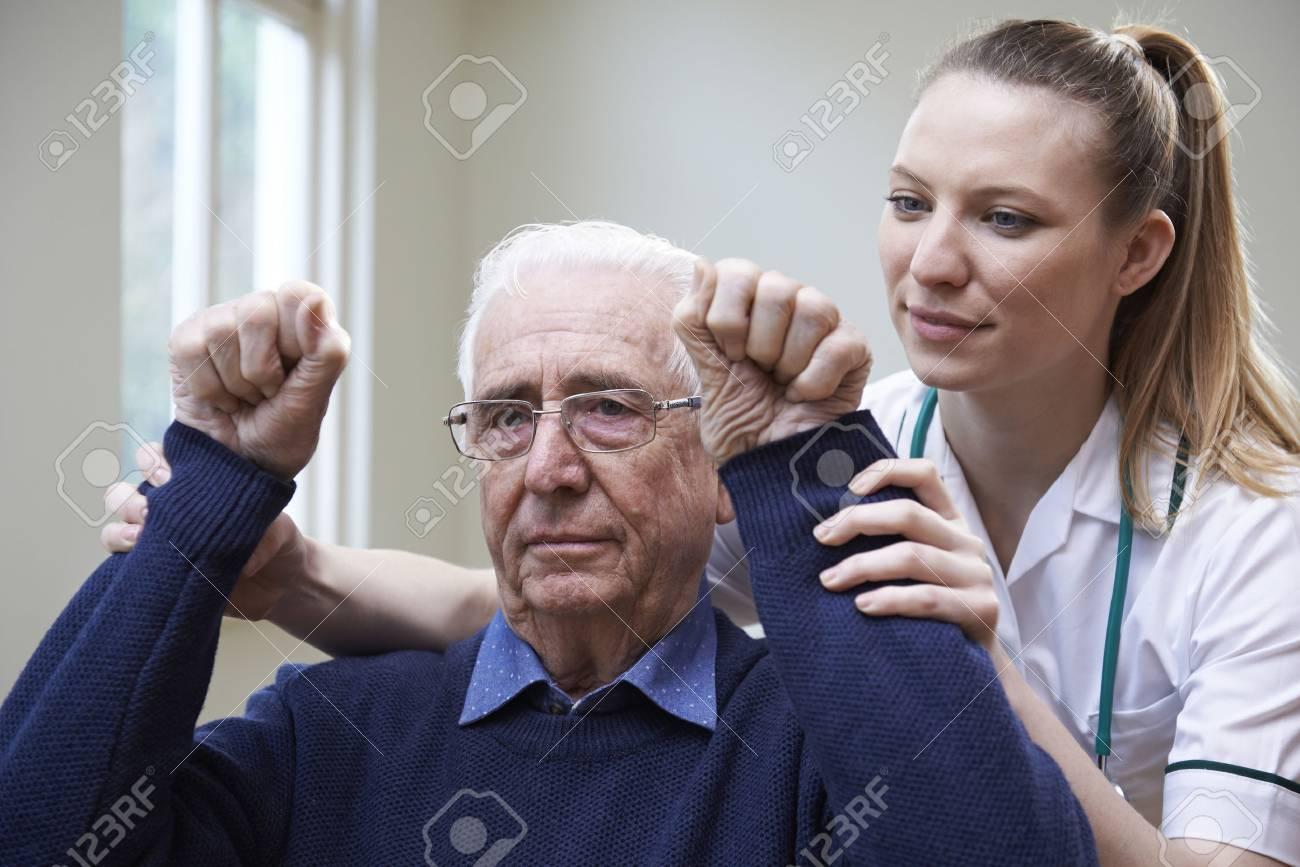 Nurse Assessing Stroke Victim By Raising Arms - 73165613