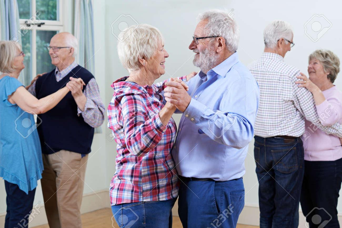 Group Of Seniors Enjoying Dancing Club Together - 75018704