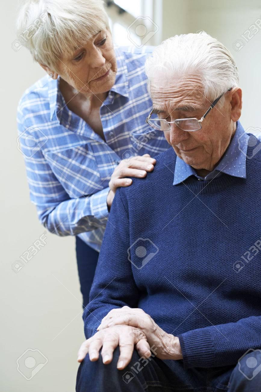 Senior Woman Comforts Husband Suffering With Parkinsons Diesease - 76501896