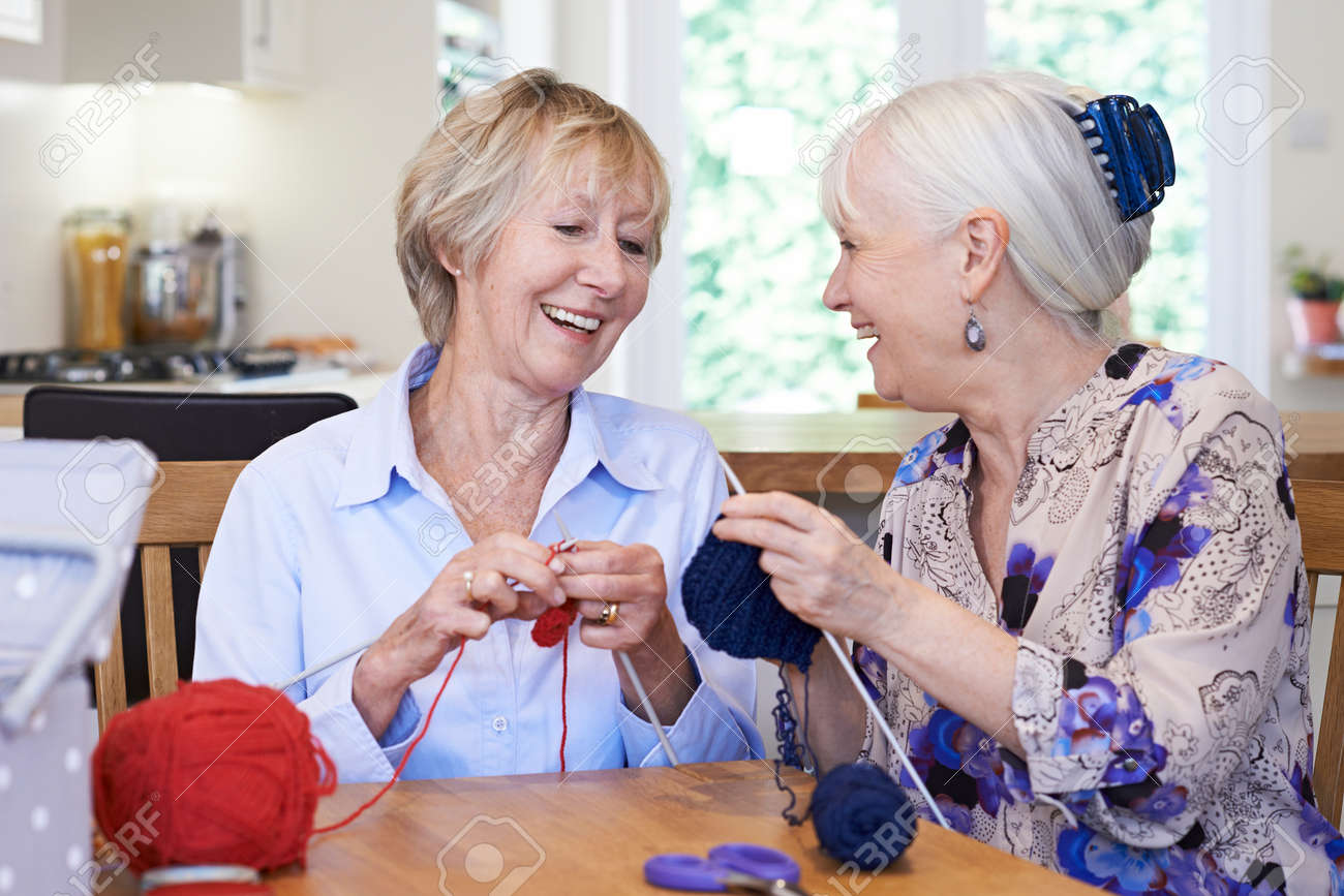 Two Senior Female Friends Knitting At Home Together - 78664224