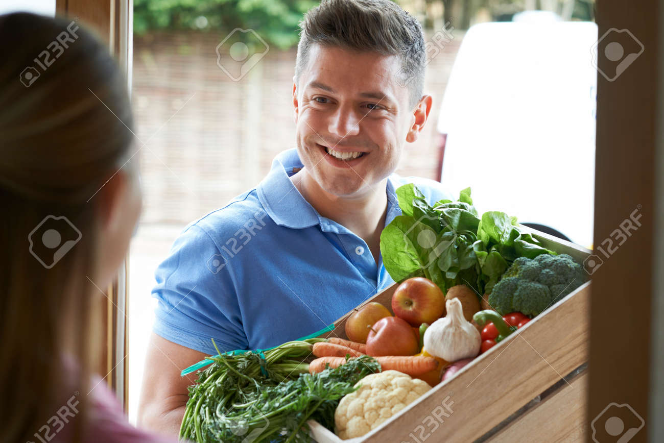 Man Making Home Delivery Of Organic Vegetable Box - 79619793