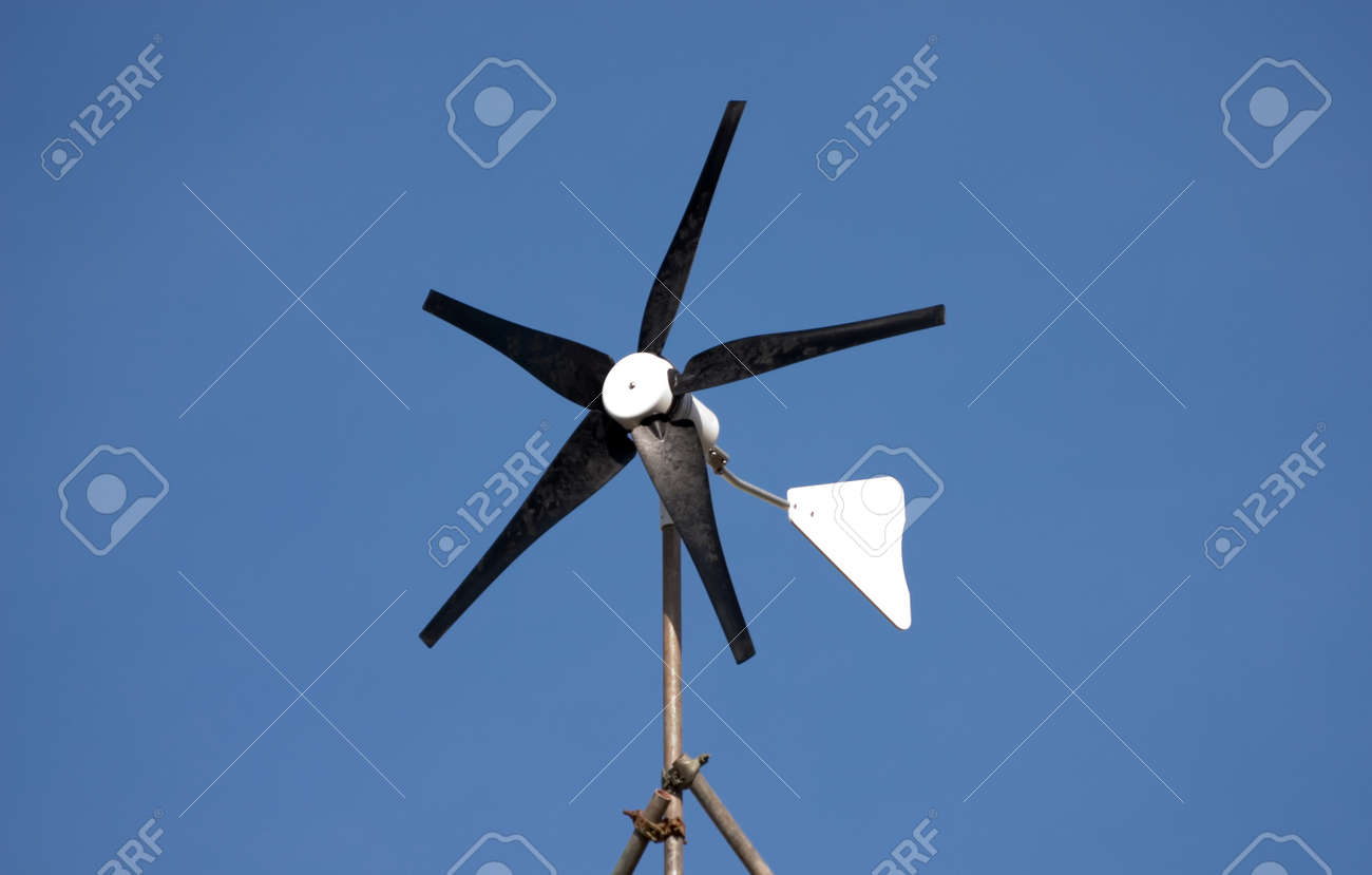 Imagens   Small Domestic Wind Turbine Generator Mounted On A Vertical Frame  Against A Clear Blue Sky