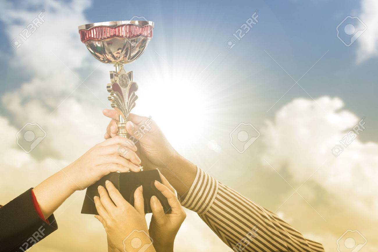 Businessman team holding award trophy for show their victory. - 65235298