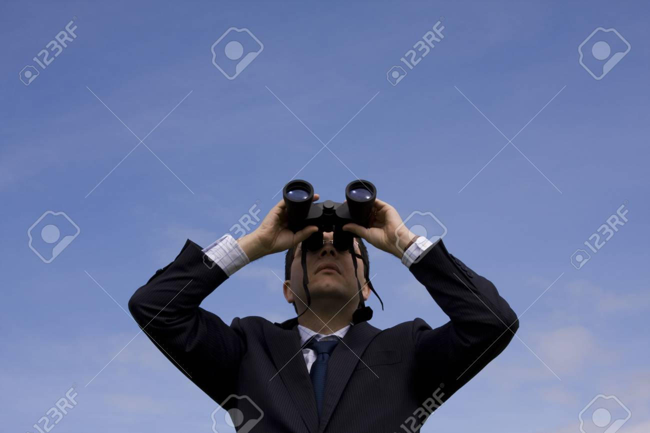 Businessman looking through binoculars with a blue sky as background Stock Photo - 2740359