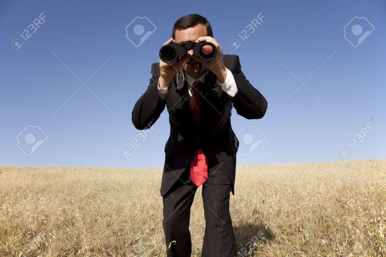 Businessman looking through binoculars at the field Stock Photo - 5469877