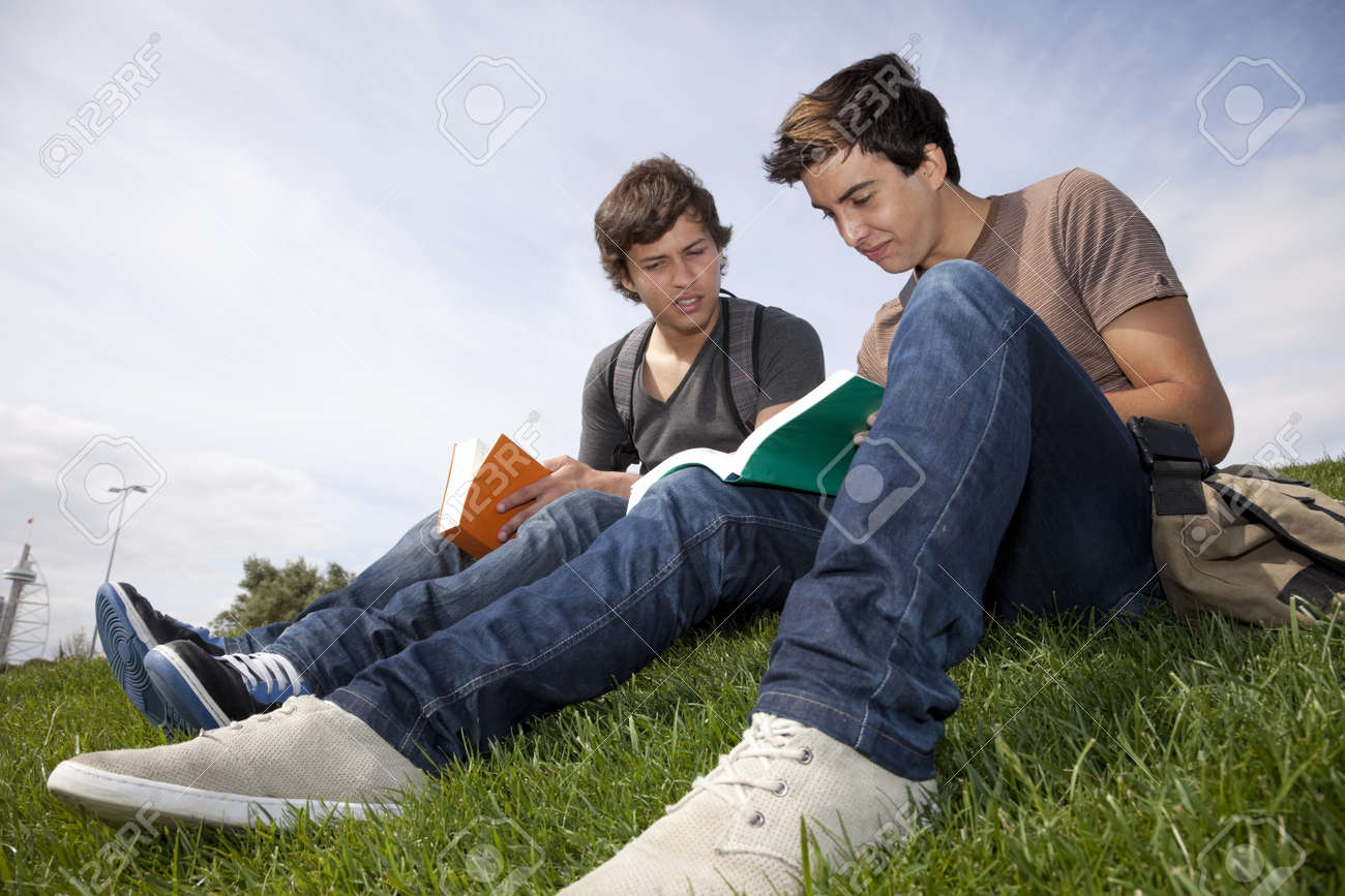 two young student reading books at the school park - 7812205