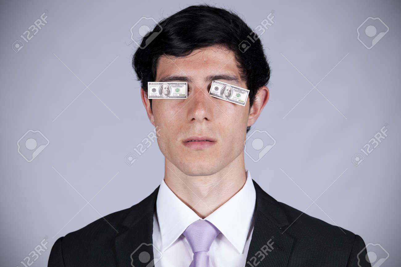 Young businessman with little dollar bills covering his eyes Stock Photo - 8174745