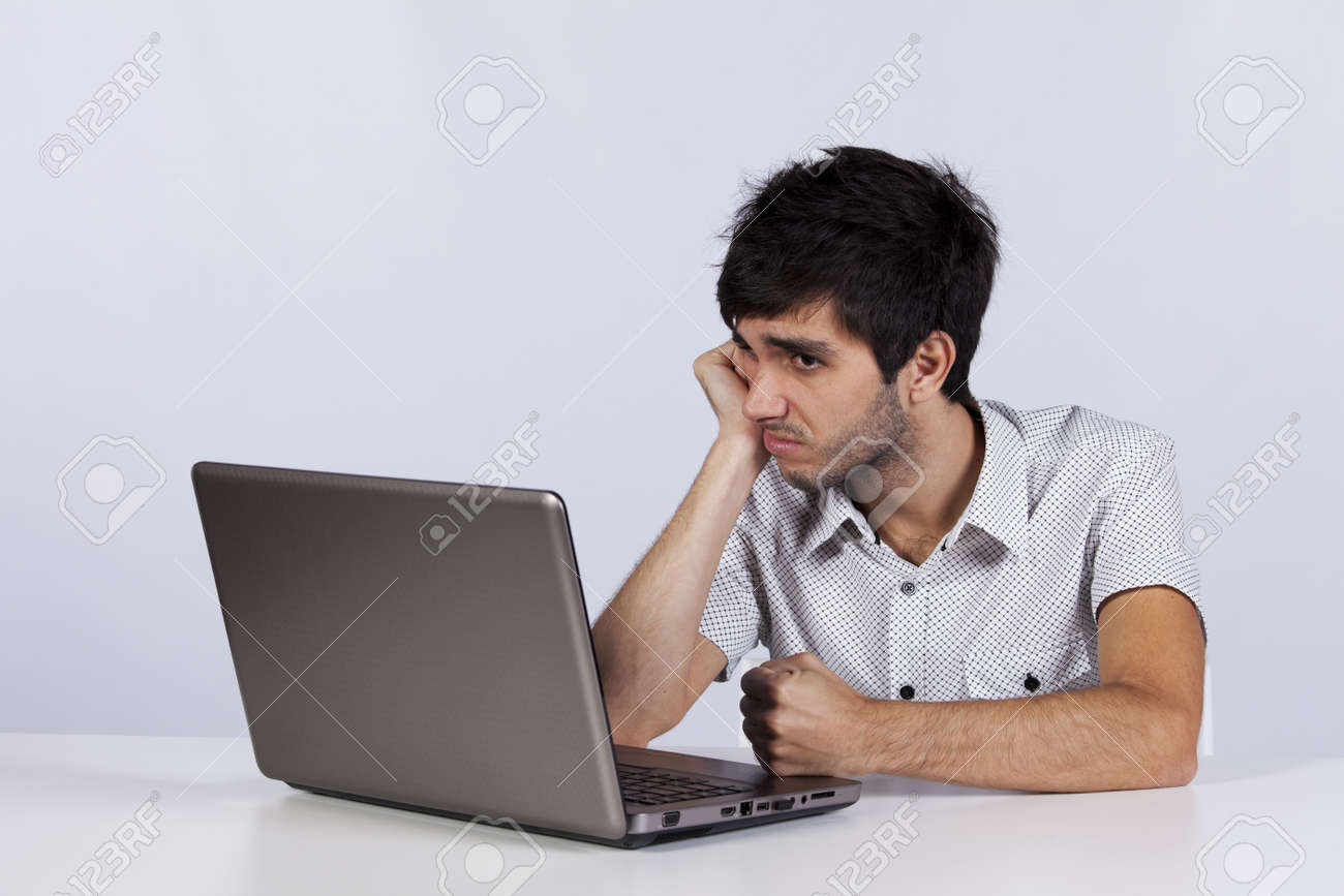 young men working with his laptop with a bored face stock photo