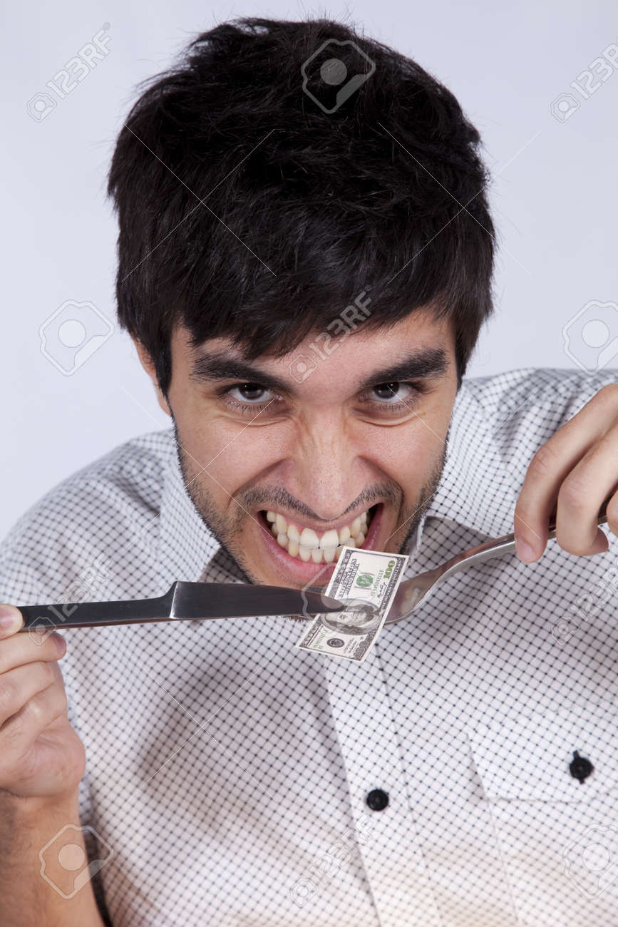 Man eating money with a fork and a knife Stock Photo - 9288603