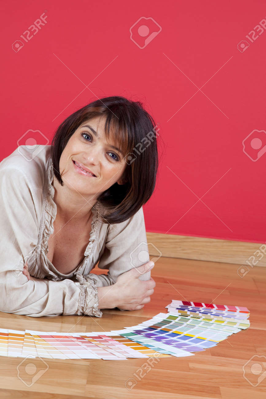 woman next to a red wall looking to a color paint palette (selective focus) Stock Photo - 10035725