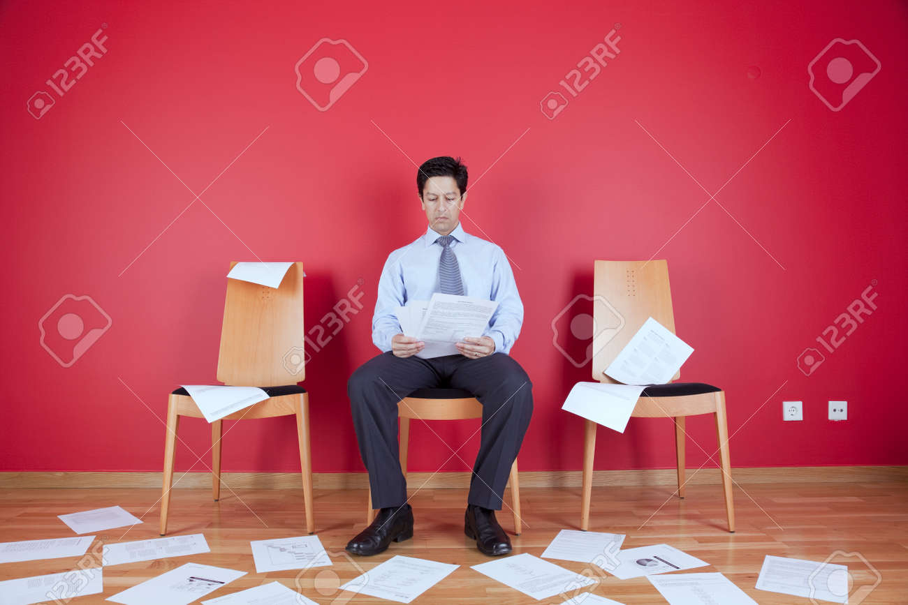 Businessman reading a document in a messy office full of papers on the floor Stock Photo - 10035755