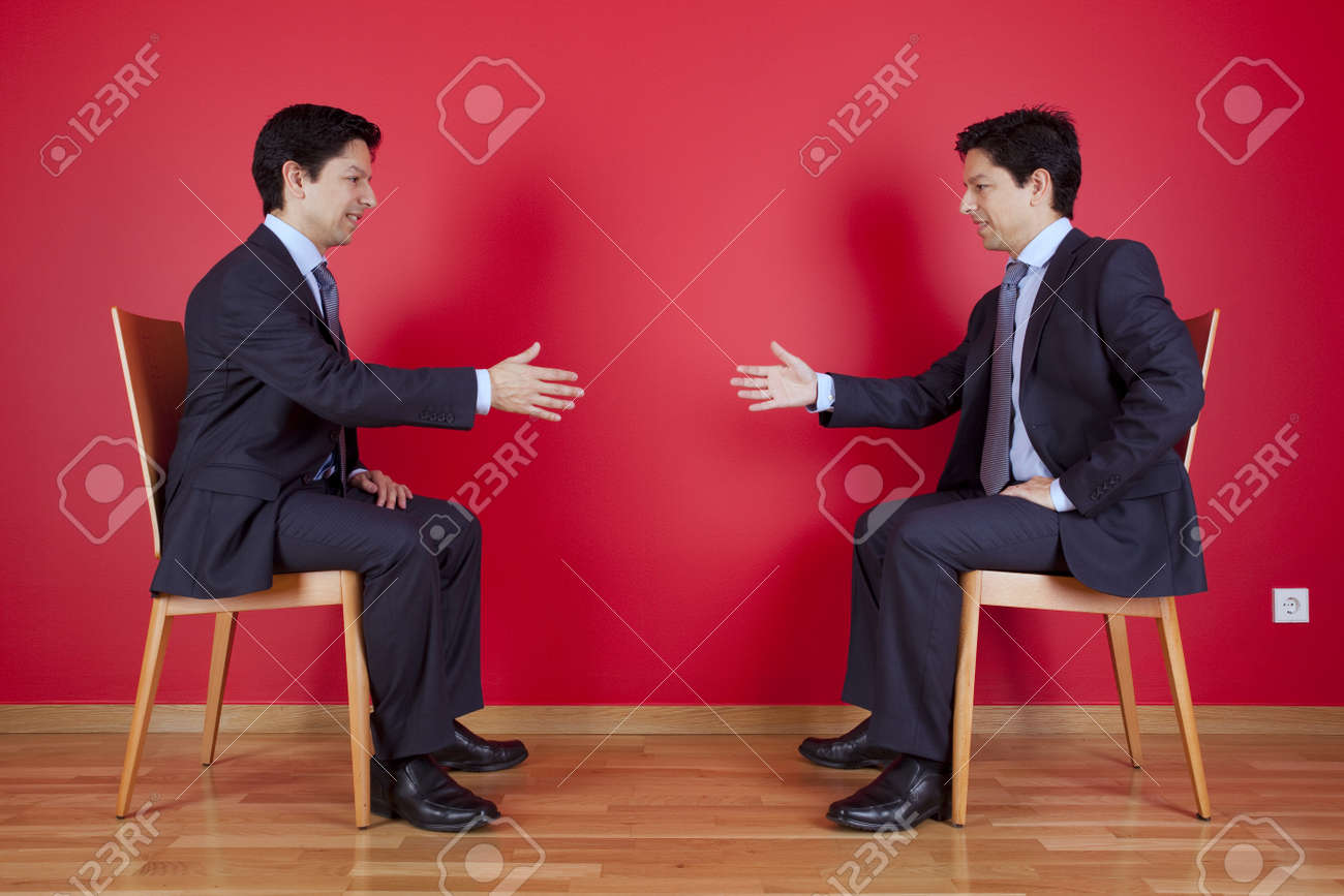 Handshake agreement between two twin businessman sitting in a chair next to a red wall Stock Photo - 10048398