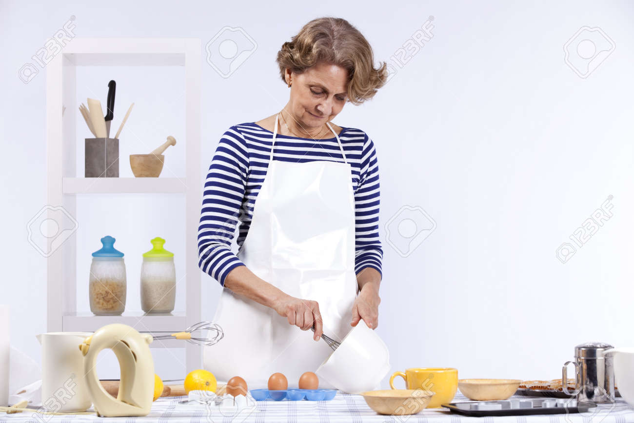 Beautiful and happy senior woman cooking at her kitchen Stock Photo - 10035849