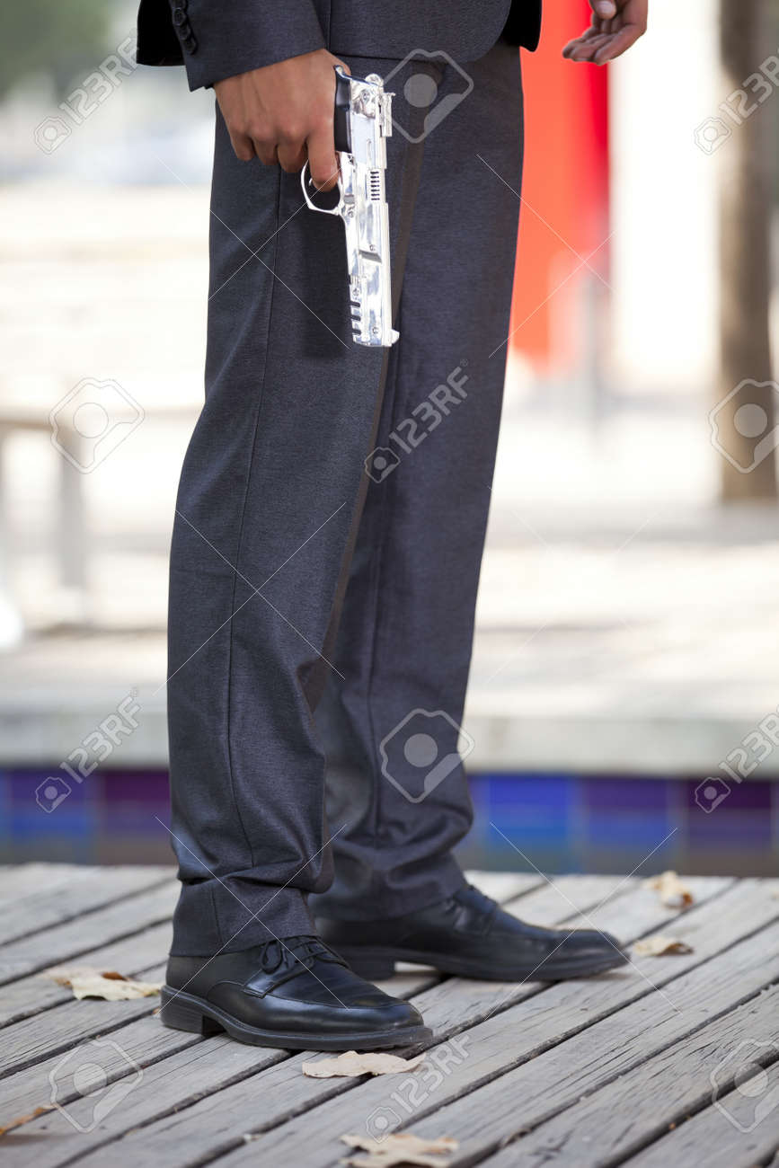 Businessman with a handgun aiming his own foot Stock Photo - 16389039