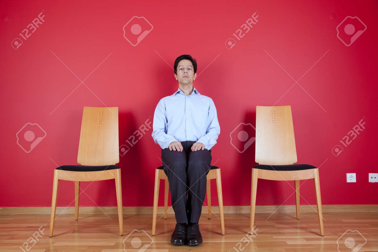 Businessman sited next to a red wall Stock Photo - 16389204
