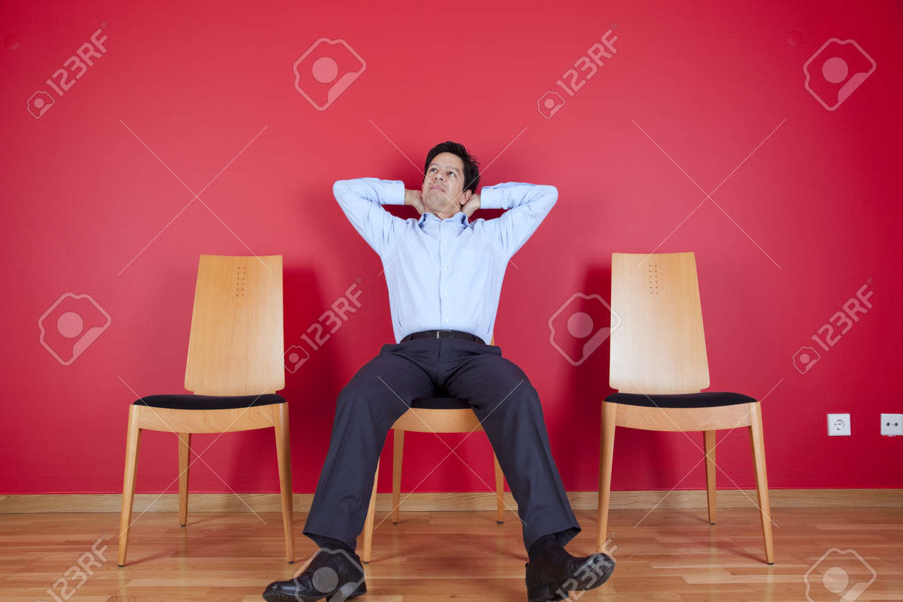 Businessman sited next to a red wall Stock Photo - 16373615